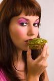 La ragazza mangia una torta Fotografie Stock