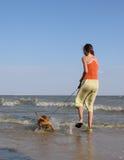 La ragazza, mare dell'estremità di cane Fotografia Stock
