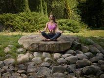 La ragazza meditates nella posizione di loto Fotografia Stock