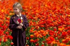 La ragazza meravigliosa sveglia del bambino del bambino cammina in un prato di fioritura della molla immagini stock
