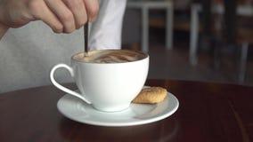 La ragazza mescola lo zucchero in una tazza di caffè La femmina passa il primo piano con il caffè della tazza stock footage