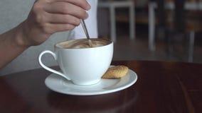 La ragazza mescola lo zucchero in una tazza di caffè La femmina passa il primo piano con il caffè della tazza video d archivio