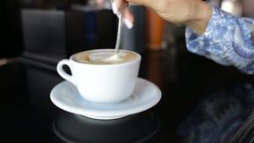 La ragazza mescola lo zucchero in una tazza di caffè La femmina passa il primo piano con la tazza di caffè archivi video