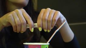 La ragazza mescola lo zucchero in una tazza di caffè Mani femminili con la tazza del americano archivi video