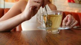 La ragazza mescola lo zucchero in una tazza trasparente con tè verde 4k, movimento lento archivi video