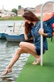 La ragazza mette il suo piede nella ritenzione di acqua sopra all'inferriata Fotografia Stock Libera da Diritti