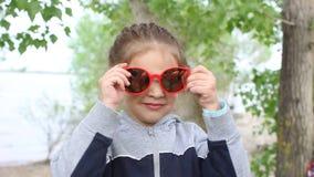 La ragazza mette sopra gli occhiali da sole all'aperto archivi video