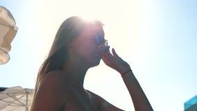 La ragazza mette sopra i suoi occhiali da sole archivi video