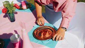 La ragazza mette sopra un coltello di plastica e una forcella della tavola festiva Fine in su archivi video