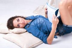 La ragazza mette sul pavimento e legge il libro Immagine Stock