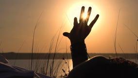 La ragazza mette sull'erba ed il contatto della luce solare a mano sopra il bello fondo del cielo Tramonto sopra l'acqua calma archivi video