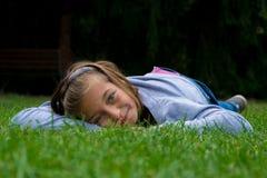 La ragazza mette sullo stomaco nel sorridere dell'erba Immagini Stock Libere da Diritti