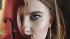 La ragazza misteriosa apre l'occhio ed esamina la macchina fotografica con il violino la parte del fronte archivi video