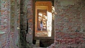 La ragazza misteriosa nel bianco scompare in un vecchio castello rovinato stock footage