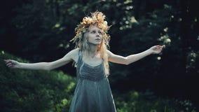 La ragazza mistica nel legno tiene un rituale Si è vestita in vestiti lunghi con la corona sulla testa Streghe, esoteriche archivi video