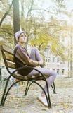 La ragazza moderna si siede pensively su un banco nel parco Fotografia Stock