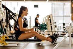 La ragazza mora atletica vestita negli sport neri superiori e mette sta risolvendo sulla macchina di esercizio nella palestra fotografia stock