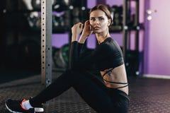 La ragazza mora atletica vestita in vestiti neri di sport si siede sul pavimento nella palestra vicino all'attrezzatura di sport fotografia stock libera da diritti