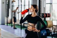 La ragazza mora esile vestita nelle bevande nere degli abiti sportivi innaffia nella palestra vicino all'attrezzatura di sport fotografie stock libere da diritti