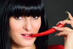 La ragazza morde il pepe caldo Immagine Stock Libera da Diritti