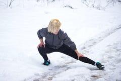 La ragazza mostra ad esercizio una cordicella nell'inverno Fotografia Stock