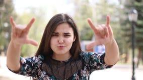 La ragazza mostra i corni con le sue dita in parco archivi video