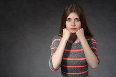 La ragazza mostra la concentrazione contro un fondo scuro Immagini Stock Libere da Diritti