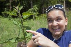 La ragazza mostra le foglie dell'ortica bruciante Fotografia Stock