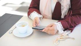 La ragazza musulmana compone un numero su un telefono cellulare archivi video