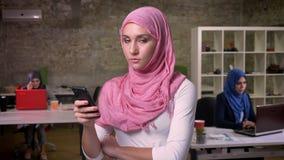 La ragazza musulmana piacevole che indossa il hijab rosa è stante e tenente il suo smartphone in ufficio moderno, ragazze di Medi archivi video