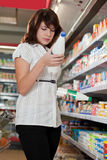 La ragazza in negozio sceglie il latte Fotografia Stock Libera da Diritti