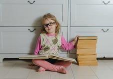 La ragazza nei punti con il libro che si siede sul pavimento Immagine Stock Libera da Diritti