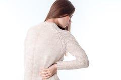 La ragazza nei supporti del maglione con il suo di nuovo alla macchina fotografica tiene la mano dal lato di dolore di sensibilit Immagini Stock