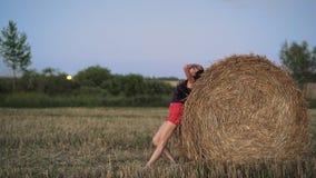 La ragazza nel campo spinge un mucchio di fieno stock footage