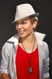 La ragazza nel cappello bianco su fondo grigio immagini stock
