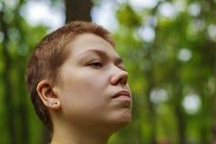 La ragazza nel giardino che odora un fiore Fotografie Stock