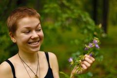 La ragazza nel giardino che odora un fiore Fotografie Stock Libere da Diritti