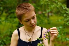 La ragazza nel giardino che odora un fiore Immagini Stock Libere da Diritti