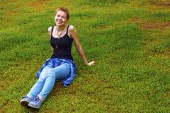 La ragazza nel giardino che odora un fiore Fotografia Stock Libera da Diritti