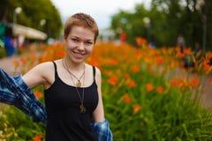 La ragazza nel giardino che odora un fiore Immagini Stock
