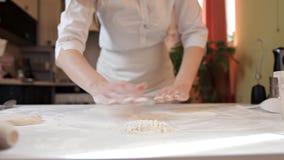 La ragazza nel grembiule srotola la pasta della pizza con un matterello Cucinando pizza a casa archivi video