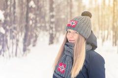 La ragazza nel legno freddo di inverno in un cappuccio ed in una sciarpa con Fotografia Stock