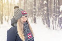 La ragazza nel legno freddo di inverno in un cappuccio ed in una sciarpa con Immagine Stock Libera da Diritti