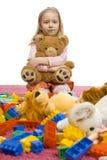 La ragazza nel mezzo di giocattolo-scompiglia Fotografie Stock Libere da Diritti