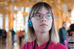 La ragazza nel museo attentamente ascolta la guida immagini stock