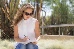 La ragazza nel parco con un taccuino e una penna Fotografie Stock