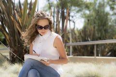 La ragazza nel parco con un taccuino e una penna Fotografie Stock Libere da Diritti