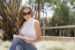 La ragazza nel parco con un taccuino e una penna Immagine Stock Libera da Diritti