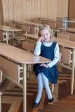 La ragazza nel primo grado, sta sedendosi allo scrittorio Fotografia Stock Libera da Diritti
