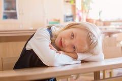 La ragazza nel primo grado, sta sedendosi allo scrittorio Immagine Stock Libera da Diritti